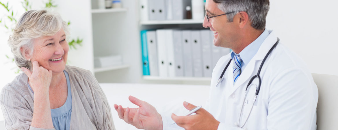 36413529 - happy male doctor discussing with senior patient at table in clinic