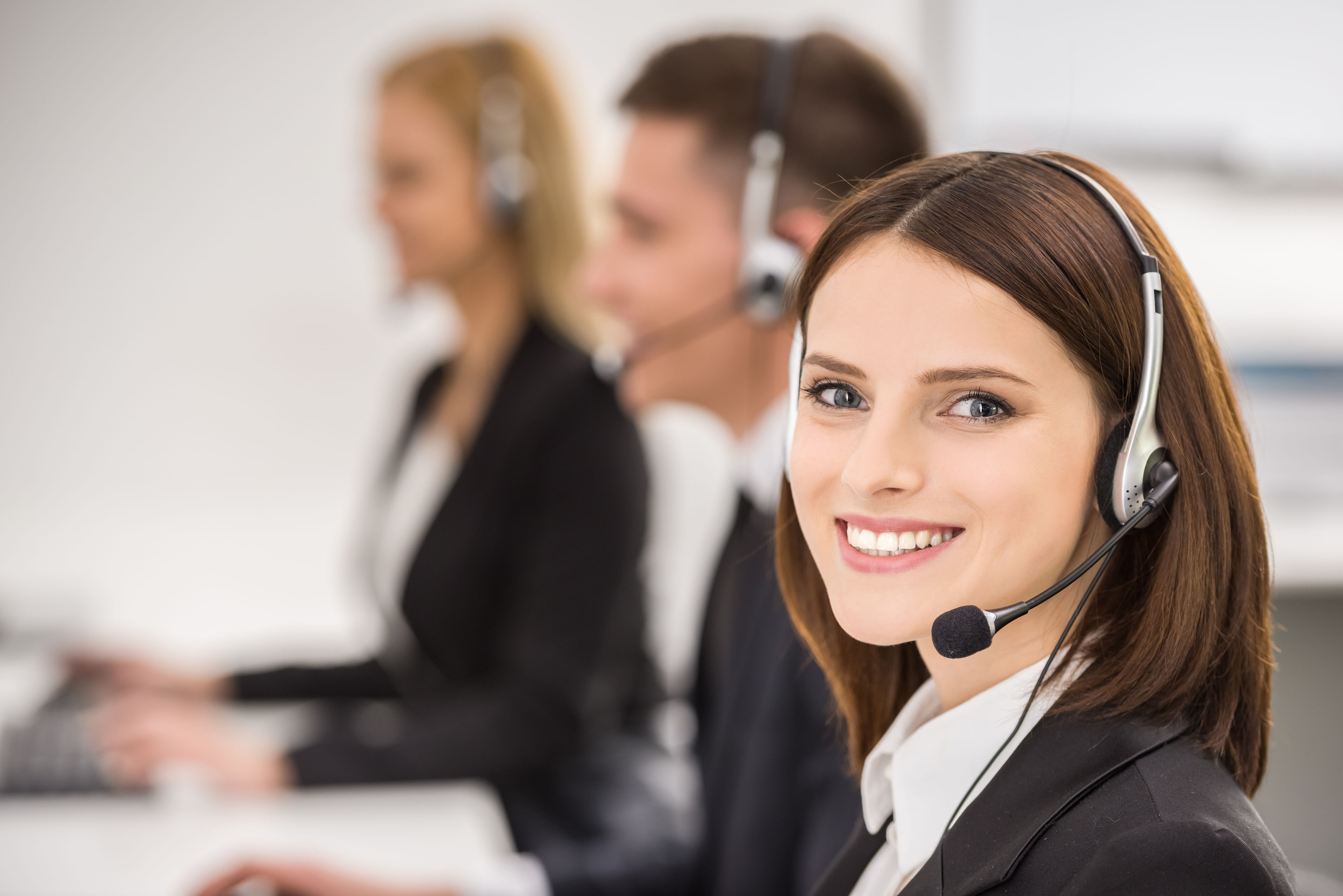 41409858 - smiling beautiful lady working at call center with colleagues in office.